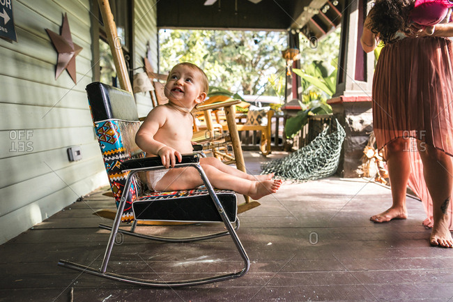 Baby wearing a diaper and rocking in a rocking chair on porch