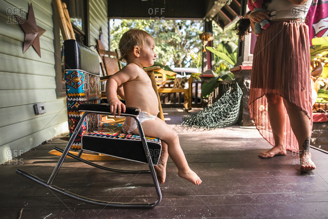 Baby in a diaper and rocking in a rocking chair on porch