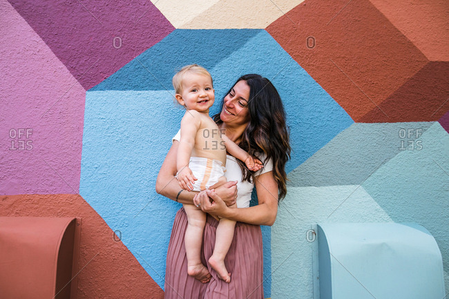 Mom holding diapered baby in front of colorful wall