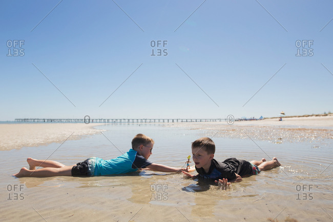 Two boys lying in the ocean tide playing together