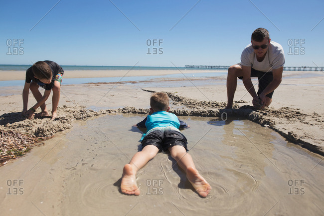 Father and two boys playing on the beach