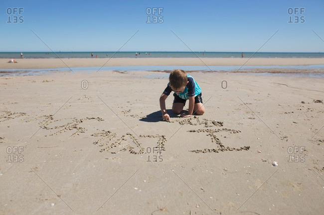 Boy writing words in the sand with his finger