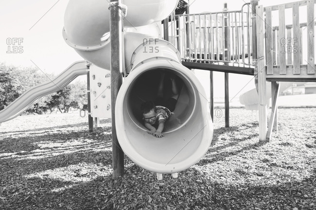 Boy sliding down tunnel slide in black and white