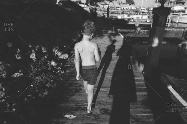 Rear view of boy walking on boardwalk in black and white
