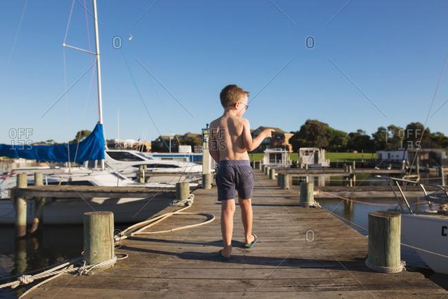 Rear view of boy walking on boardwalk