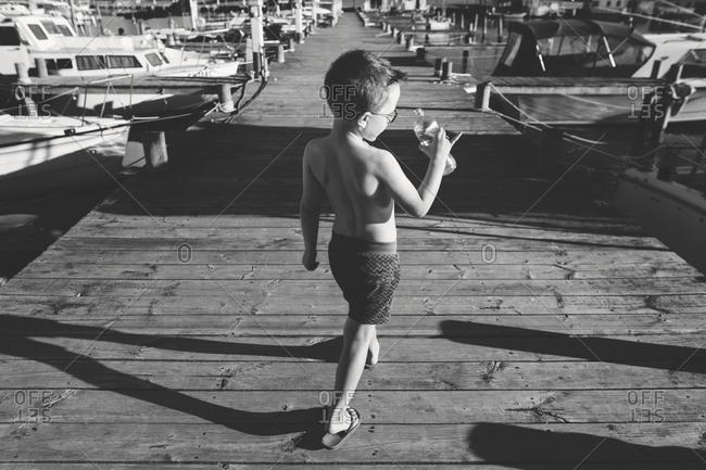 Rear view of boy walking on boardwalk with water bottle in black and white