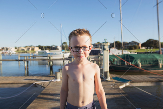 Portrait of young boy with glasses on boardwalk