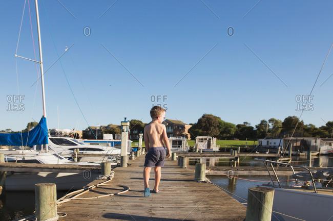 Boy walking on boardwalk from behind