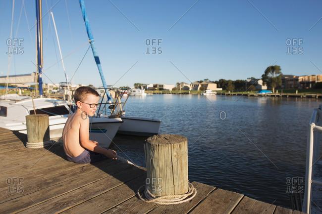 Boy sitting by boat on boardwalk