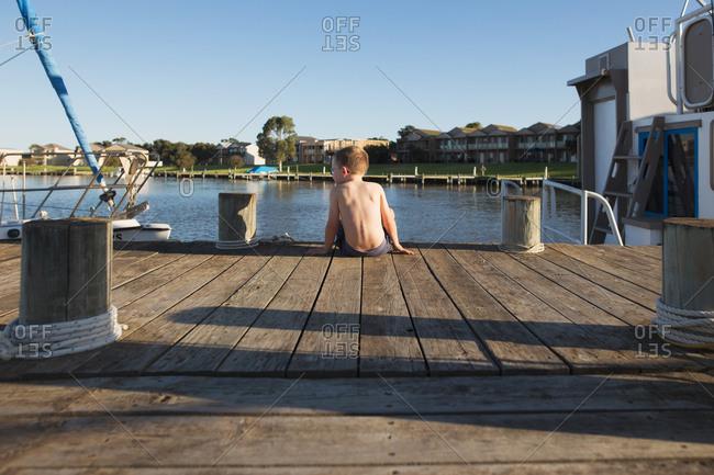 Rear view of boy sitting by boat on boardwalk