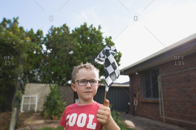 Young boy with glasses waving a checkered racing flag