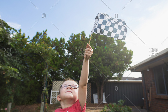 Young boy with glasses holding a checkered flag up in the air