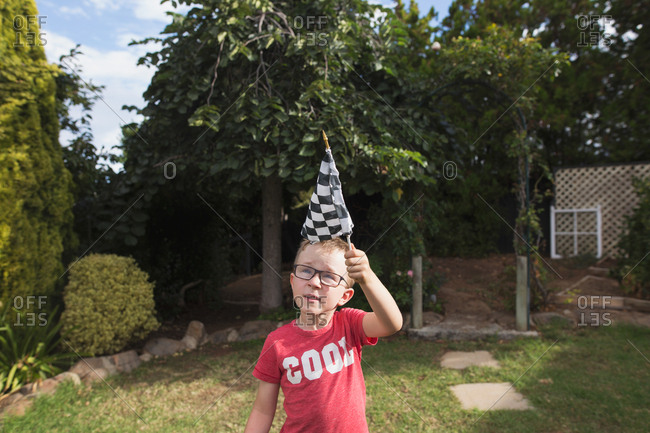Boy with glasses waving a checkered racing flag