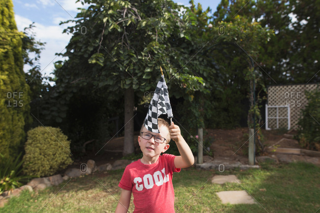 Little boy with glasses waving a checkered racing flag