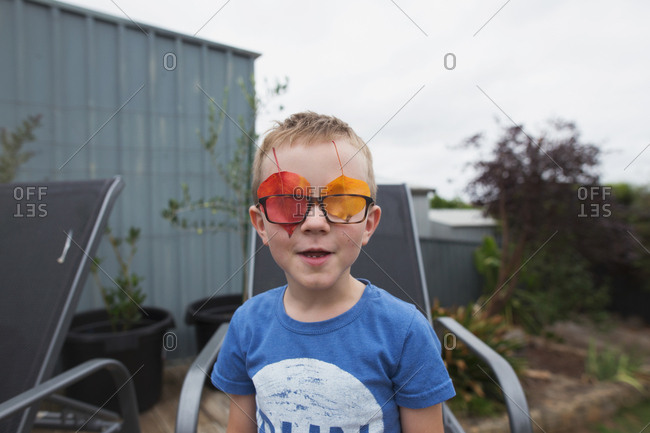 Little boy with colorful leaves behind his glasses