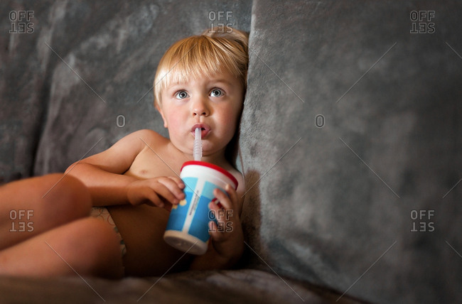 Toddler on couch with cup