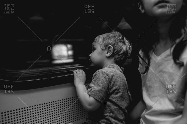 Toddler looking out subway train
