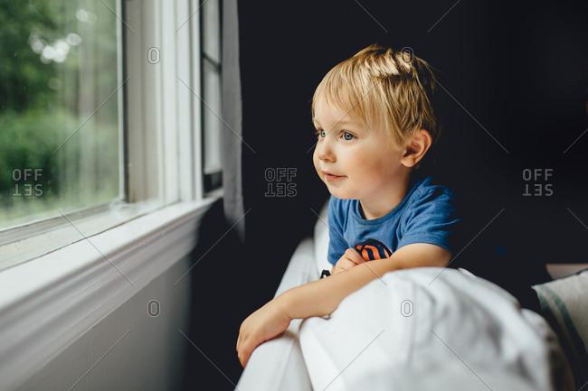 Boy with blue eyes gazing out a window