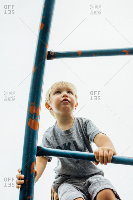 Blonde boy climbing playground ladder