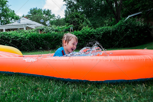 Boy on backyard water slide