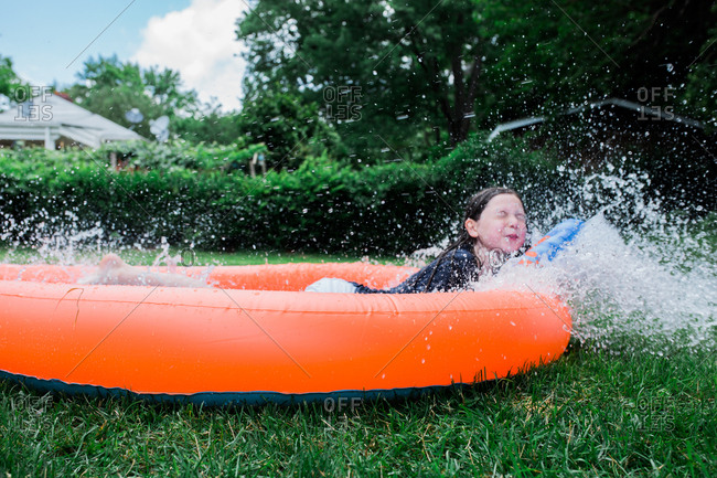 Girl splashing on water slide