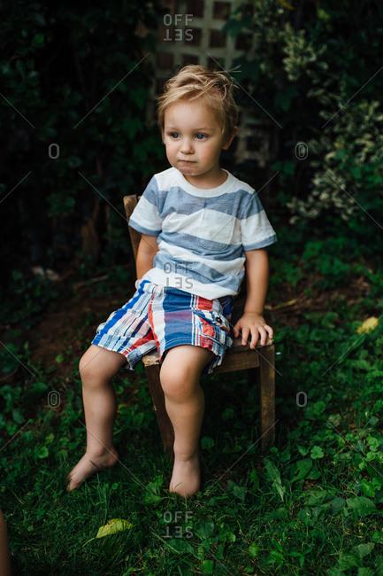 Boy sitting in small chair in yard