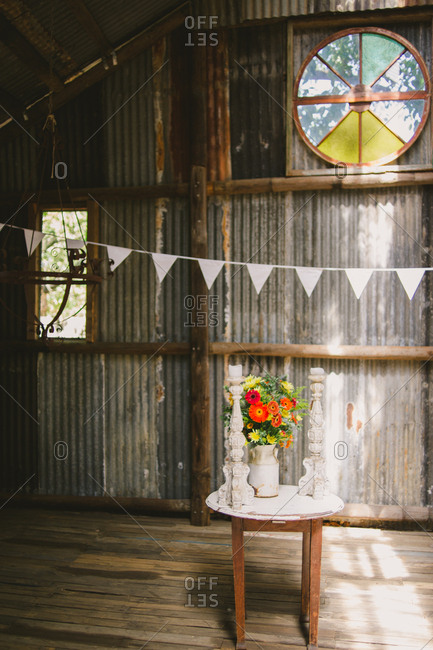 Table with flowers and candles at a rustic wedding ceremony