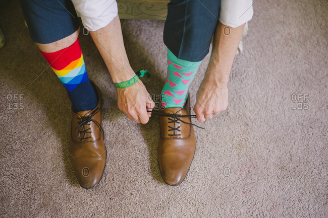Groom wearing mismatched socks tying his shoes
