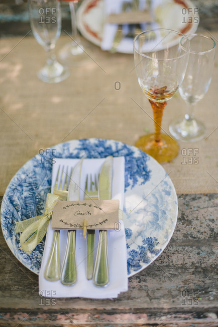 Plate with a nametag on rustic wood outdoor wedding table