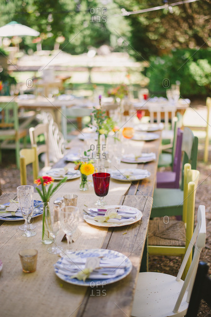 Outdoor table set for a wedding with colorful painted chairs