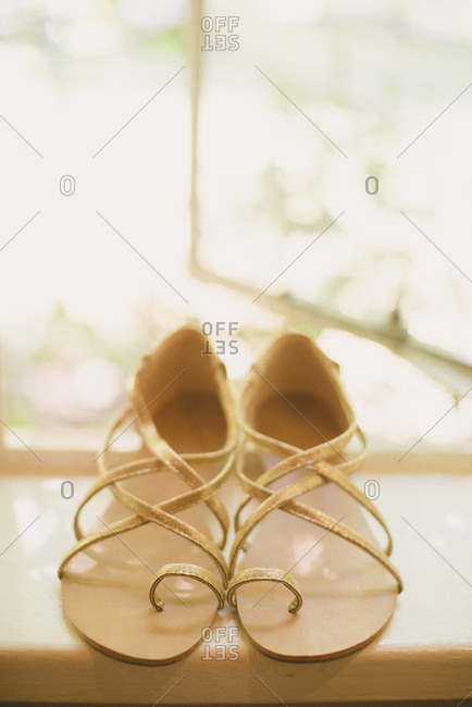 Pair of golden sandals in a window