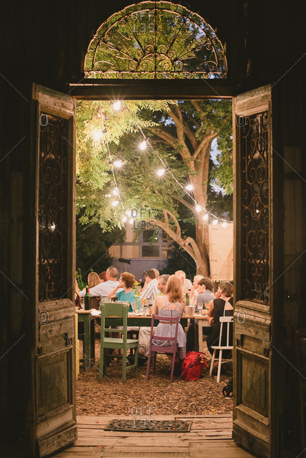 Stellenbosch, South Africa - February 4, 2017: Guests seated at outdoor tables under string lights at wedding reception