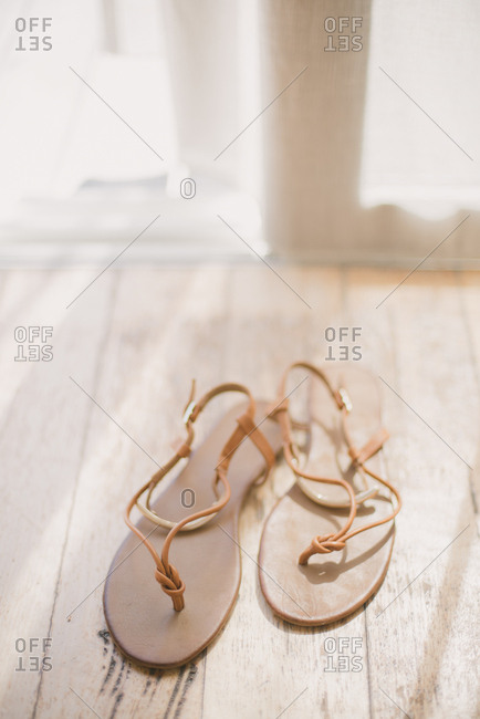 Pair of strappy sandals on a wooden floor