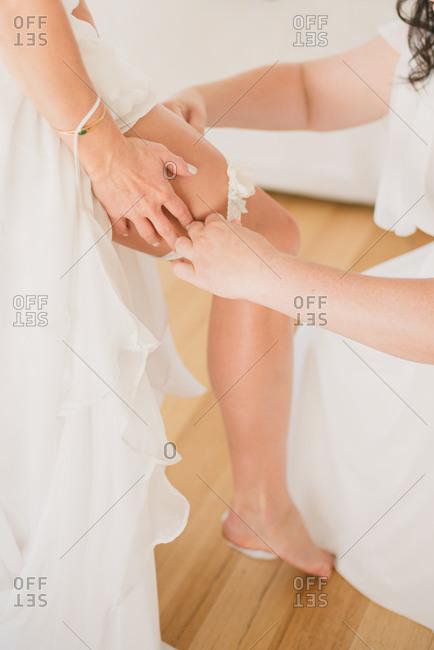 Woman helping bride put on a garter