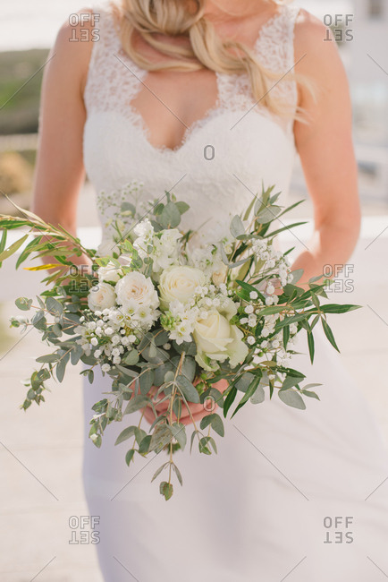 Bride on beach holding bouquet of white flowers