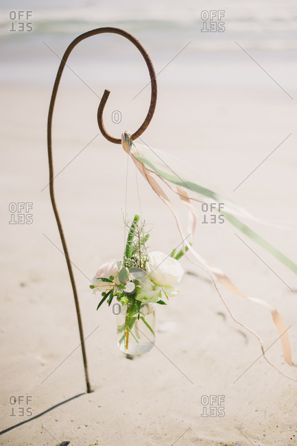 Shepherd hook holding jar of flowers on the beach in Langebaan, South Africa