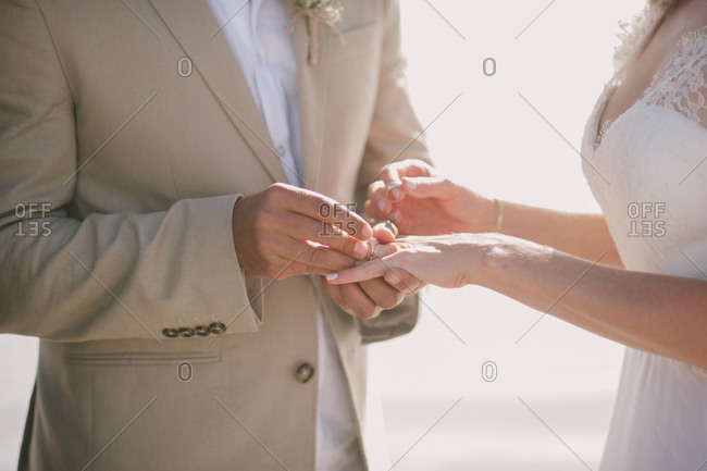 Groom putting ring on bride's finger on a beach in Langebaan, South Africa