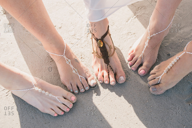 Bride and bridesmaids wearing foot jewelry on a beach