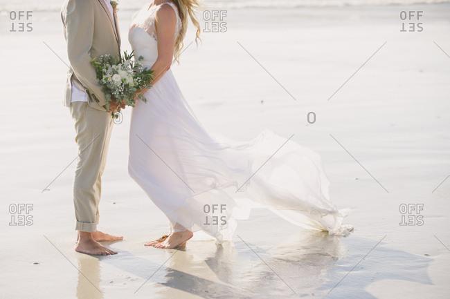 Barefoot bride and groom on beach in Langebaan, South Africa