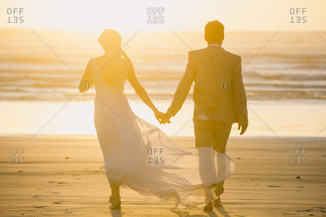 Barefoot bride and groom walking on beach at sunset