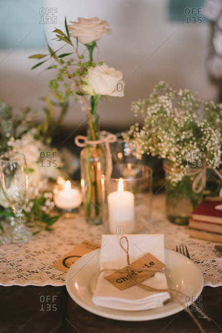 Table setting with nametag by candlelight and floral centerpieces