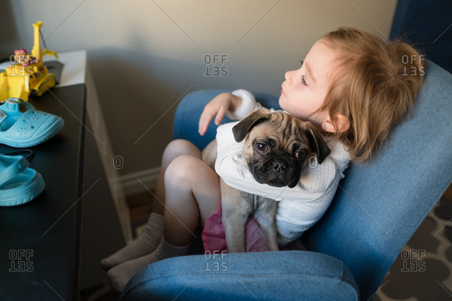 Toddler girl holding dog in chair