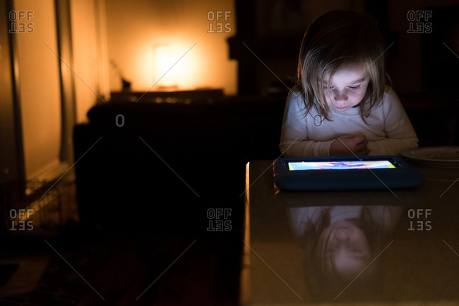 Girl in nighttime glow of a tablet