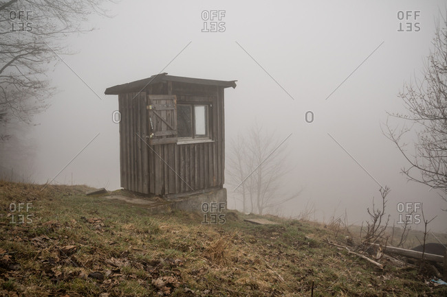 Small wooden building on hillside on foggy day