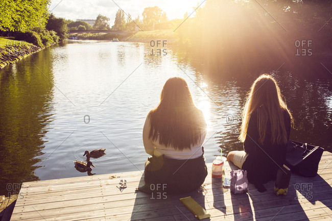 Young women sitting on pier and looking at ducks
