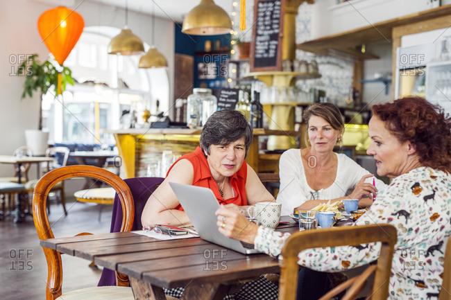 Businesswomen looking at laptop during lunch in restaurant