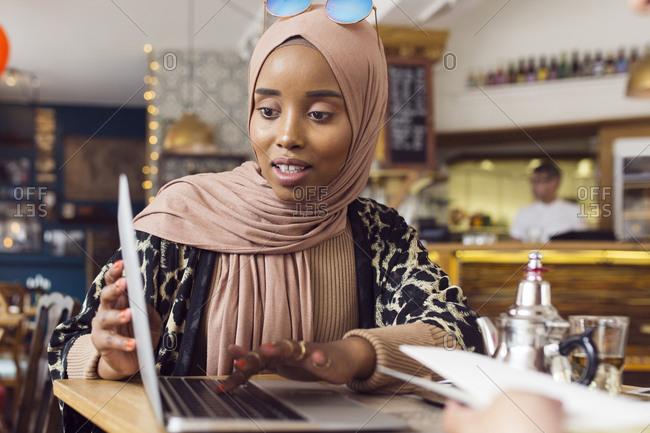 Businesswoman using laptop in tea room