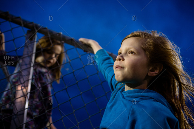 Determined young girls climbing a fence at night
