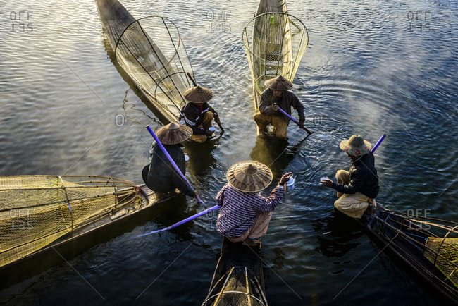 Nyaung Shwe, Shan, Myanmar - December 16, 2013: High angle view of Asian fishermen fishing in canoes on river