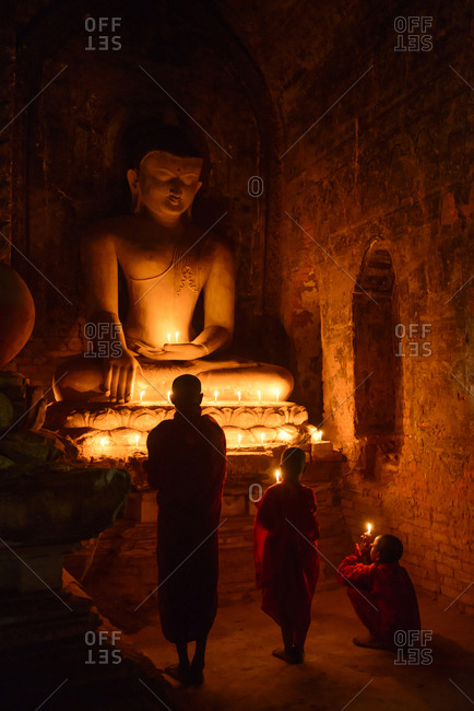 Mingun, Mandalay, Myanmar - December 21, 2013: Asian monks-in-training lighting candles at Buddha shrine